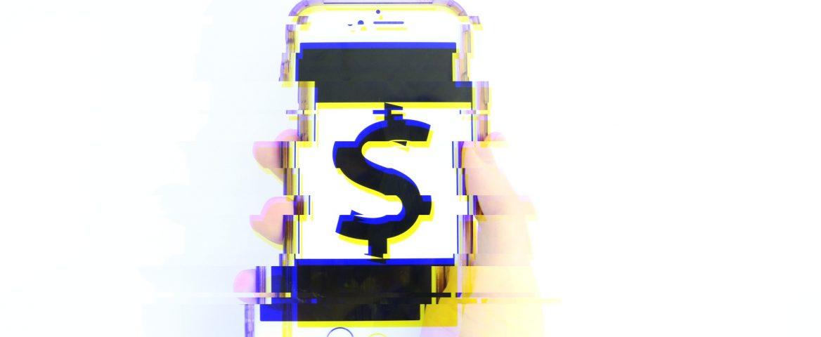 Uma mão segura um celular com uma foto de símbolo de dinheiro. A imagem foi distorcida para gerar um efeito futurístico
