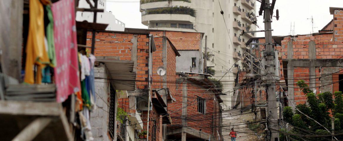 Rua e casas de Paraisópolis, uma favela de São Paulo. É possível ver os gatos de energia no poste.