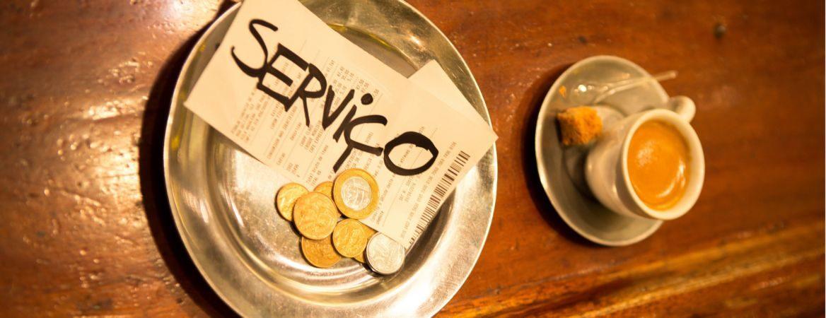 """Bandeja prata com moedas em cima de uma mesa de madeira. Há também notas fiscais em que está escrito, em preto, """"serviço. Tem também uma xícara branca com café."""