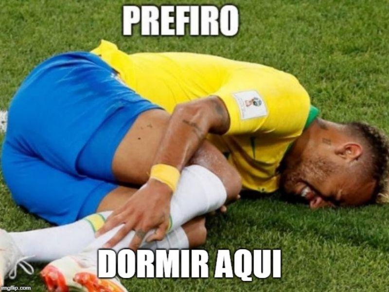 """O jogador Neymar veste com o uniforme amarelo da seleção brasileira. Ele aparece caído no chão de um campo de futebol ao centro da imagem. Ele está segurando seu tornozelo com expressão de dor. No topo da imagem em texto branco, está escrito """"prefiro"""" e na parte de baixo """"dormir aqui""""."""