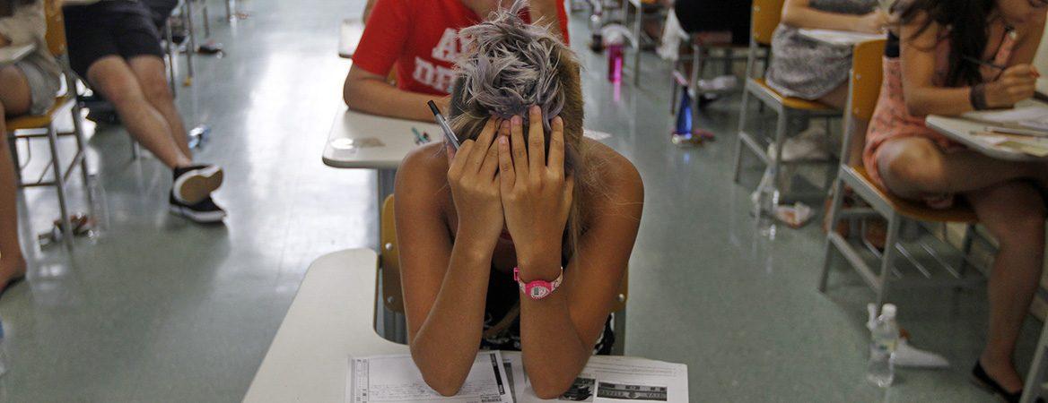 Menina em mesa, em sala de aula, prestando vestibular, com os cotovelos em cima da mesa e as mãos no rosto, com outros alunos dentro da mesma sala.