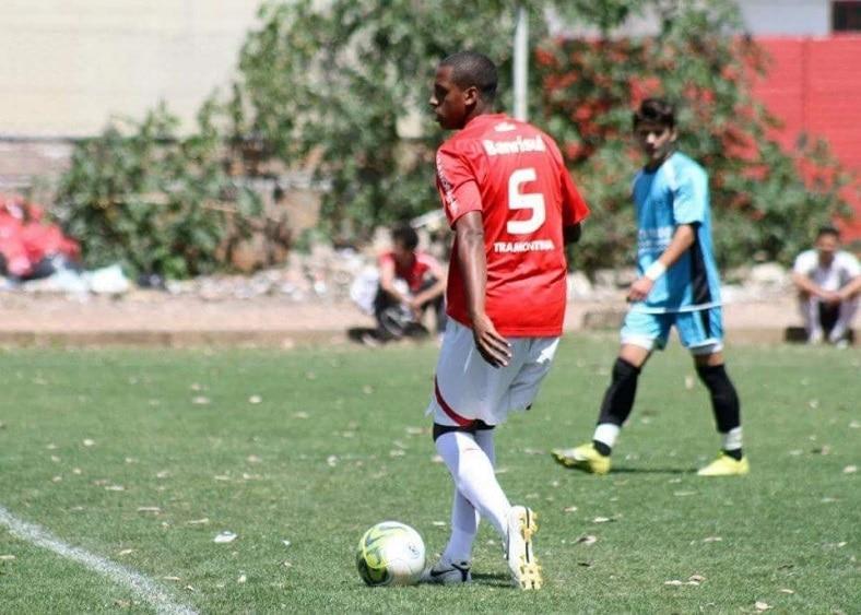 Num campo de futebol, Evandro Costa joga pela base do Internacional de Porto Alegre. Utilizando a camisa de número cinco, ele conduz a bola próximo a linha de meio-de-campo enquanto é observado de perto por um jogador do time adversário.