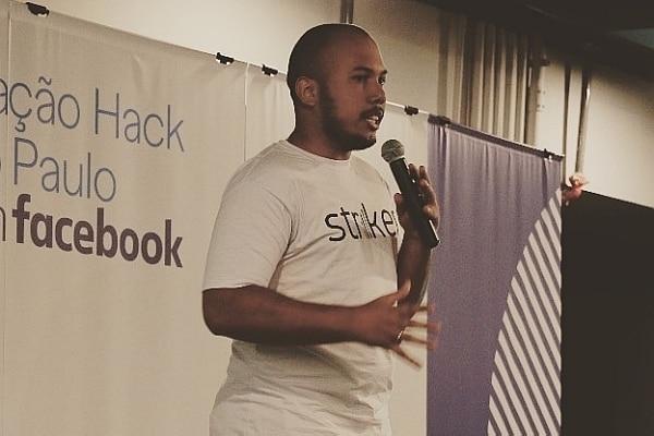 """O estudante de direito Lucas Carvalho apresenta seu projeto chamado """"Striker"""". Ele está com um microfone na mão e camiseta onde se lê """"Striker"""", nome do projeto."""