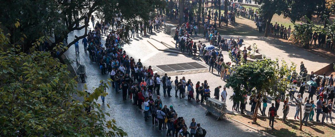 Pessoas, no vale do Anhangabaú, em São Paulo, fazendo filas, em calçadão, que fica no meio de várias árvores.