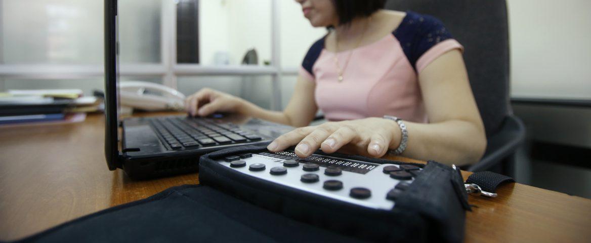 Uma mulher veste camiseta rosa bebê com mangas azul marinho. A mão esquerda dela, em destaque, está apoiada num teclado em braile. A outra mão está apoiada no notebook, que está na frente dela e em cima de uma mesa.