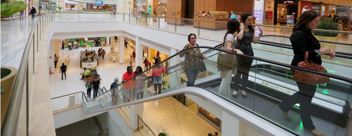 Andar de um shopping, no qual pessoas estão subindo a escada rolante.