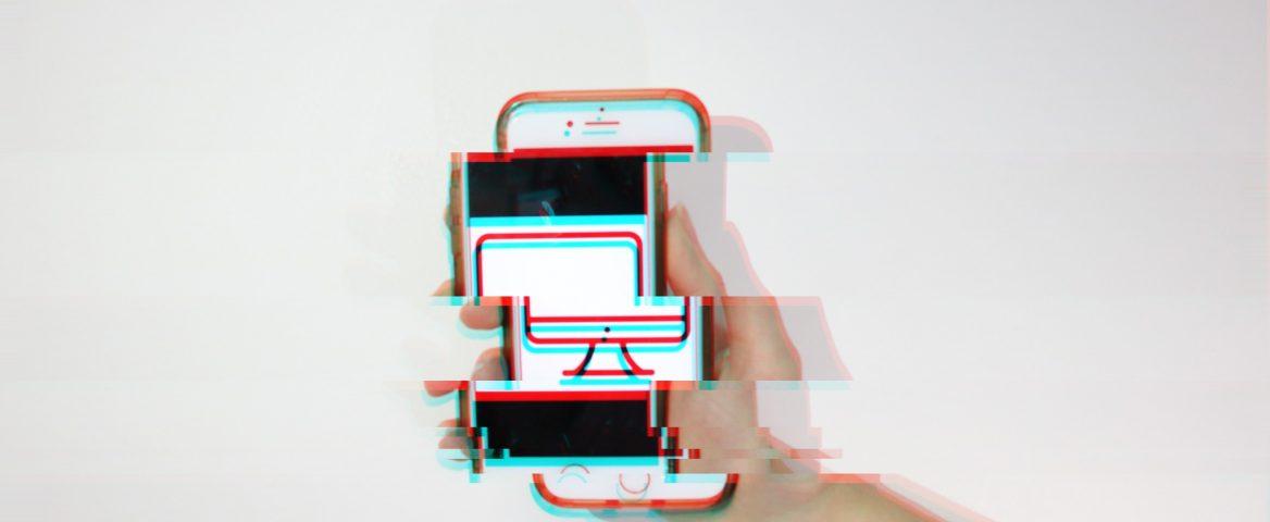 Na foto, uma mão segura um celular com uma foto com o ícone de um computador. A imagem foi distorcida para gerar um efeito futurístico