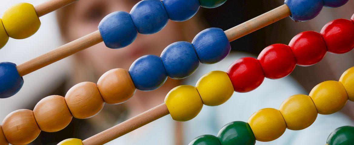 No plano de fundo, desfocado, há uma criança. No plano frontal, com foco, há um ábaco, instrumento de cálculo matemático. A moldura é de madeira e as bolinhas são coloridas, com as cores amarelo, vermelho, azul e verde.