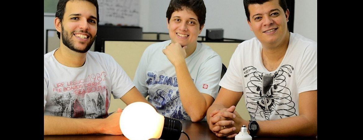 Sócios da Bluelux, vestindo camisetas informais estão sorrindo, tendo à frente uma lâmpada