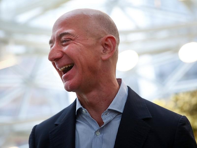 Jeff Bezos, fundador da Amazon, sorri, com o rosto em perfil. Ele é totalmente calvo e veste blazer azul marinho e camisa listrada de branco com azul