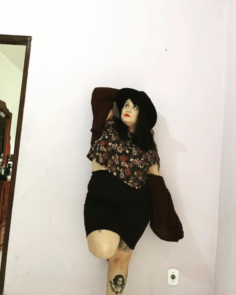 Bruna Jacquier está em pé apoiada numa parede. Ela é morena, possui cabelos longos e usa batom vermelho. Ela usa uma saia preta justa, camiseta florida e casaco marrom. Ela possui a tatuagem de busto feminino na perna direita.