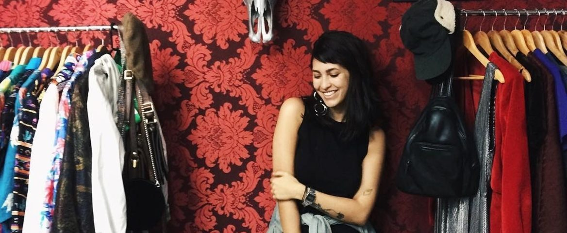 Gabrielle Lobo posa entre dois cabideiros de roupas. Ela está apoiada na parede e veste um vestido preto sem mangas com comprimento até o joelho, casaco jeans amarrado na cintura, relógio prateado e brincos grandes de argola. O cabelo dela é preto e está solto. Ela sorri.