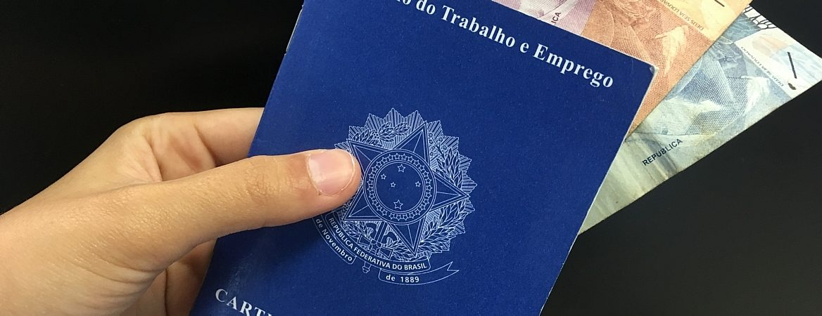 Mão segura carteira de trabalho com notas de 10, 5 e 2 reais