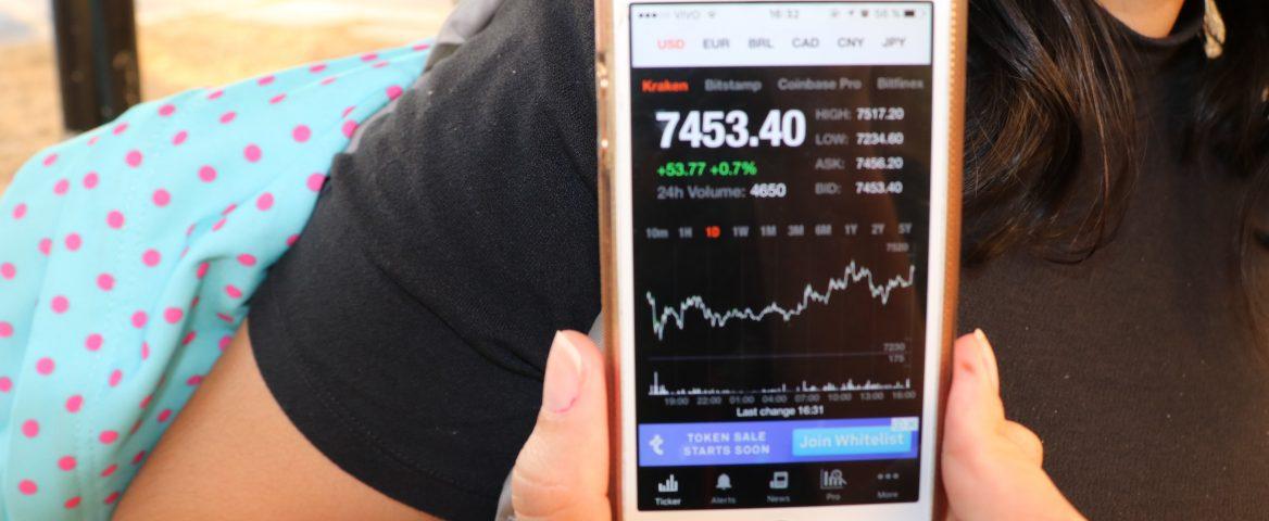 O braço de uma moça aparece na imagem. Ela segura um celular, e na tela dele aparece um valor e um gráfico que mostra oscilação do preço de uma criptomoeda. Ao fundo, é possível ver a mochila da jovem, pendurada no seu ombro.