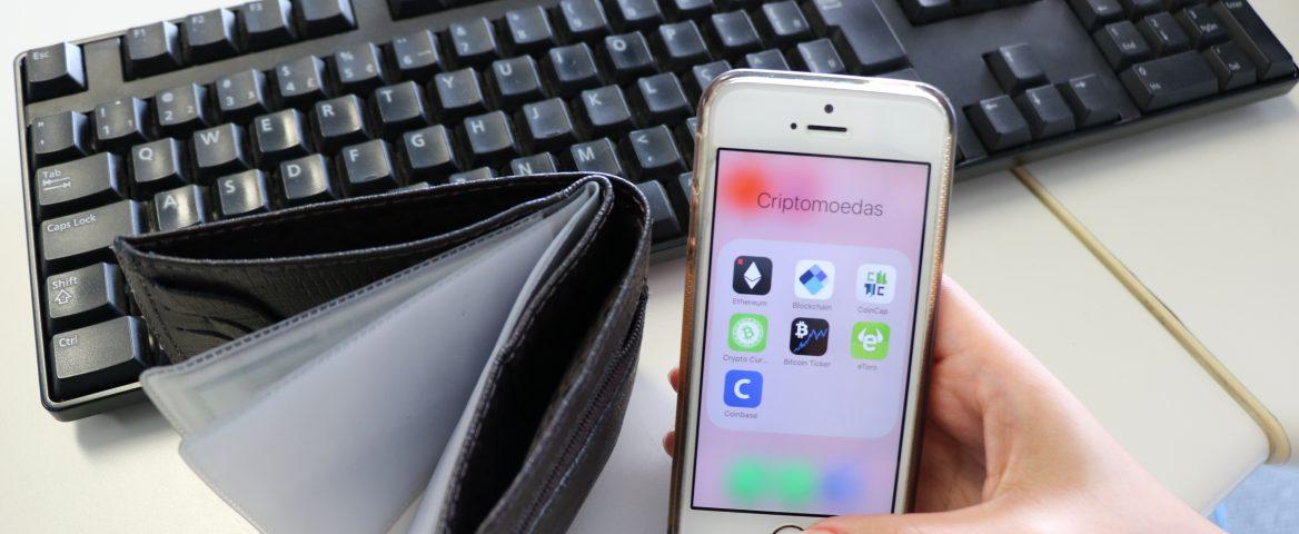 Uma mão segura um celular. Na tela, aparece uma pasta com sete aplicativos diferentes relacionados à criptomoedas. Ao lado do celular, uma carteira aberta e vazia está apoiada sob uma mesa. Ao fundo, um teclado de computador também está sob a mesa.