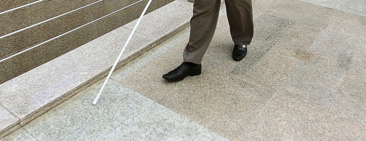 Jovem deficiente visual anda com auxílio de bengala branca. Na imagem aparecem apenas os detalhes da calça marrom, dos sapatos pretos e da bengala