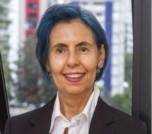 Vera Rita de Mello tem os cabelos curtos, na altura da orelha, na cor azul. Ela possui os olhos castanhos e usa batom vermelho. Ela veste camisa branca e blazer preto. Vera sorri.