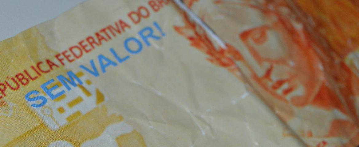 Uma nota de 20 reais amassada com rasgos no meio e na ponta, com a inscrição