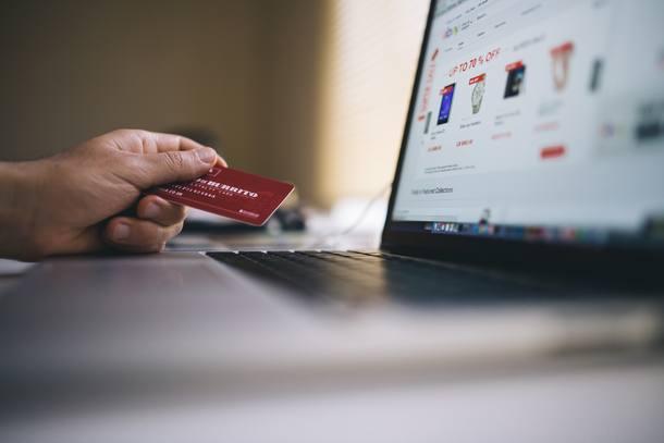 Foto de uma pessoa com seu cartão de crédito e seu computador, muito provavelmente realizando compras online.