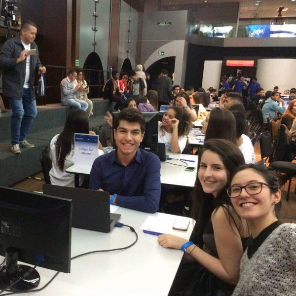 Três alunos do Colégio Albert Sabin sentados em uma mesa, na sede da B3, simulando um pregão da Bolsa de Valores, com um notebook e um monitor sobre a mesa. Ao fundo, mais alunos, de outras escolas, para participarem do desafio da B3.