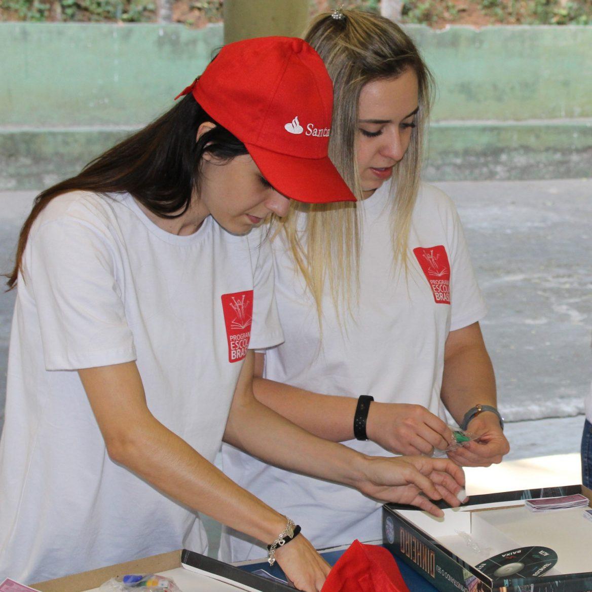 Duas instrutoras do programa Santander de educação financeira organizando materiais em cima da mesa. Na esquerda, a moça tem cabelo preto comprido. A mulher da direita é loira e tem os cabelos no ombro. Ambas vestem camiseta branca e boné vermelho com o logotipo do banco Santander.