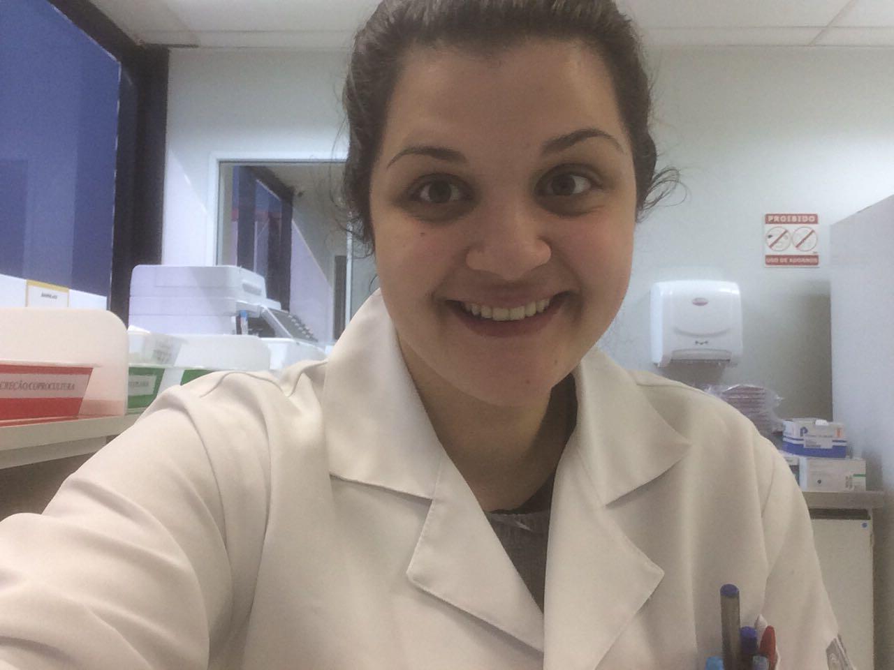 A jovem Mariana sorrindo, de cabelo preso e vestindo um jaleco branco em um laboratório de biomedicina.