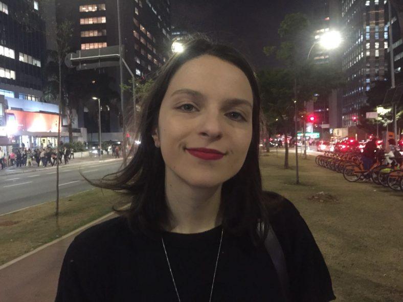 A estudante de moda Ana Carolinna Gimenez vestida com um casaco preto, tendo a Avenida Faria Lima ao fundo. É noite. Na avenida, é possível ver bicicletas, uma ciclovia e prédios.