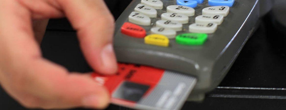 Cartão de crédito sendo inserido em uma maquininha.