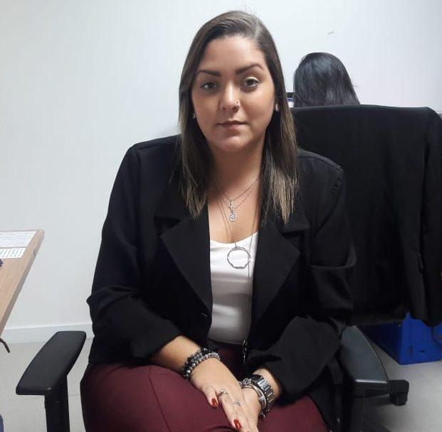 Rafaela Macau está posando para a foto sentada em uma cadeira. Ela veste blusa branca com blazer preto e calça vinho. O cabelo é castanho e está solto. Fim da descrição.