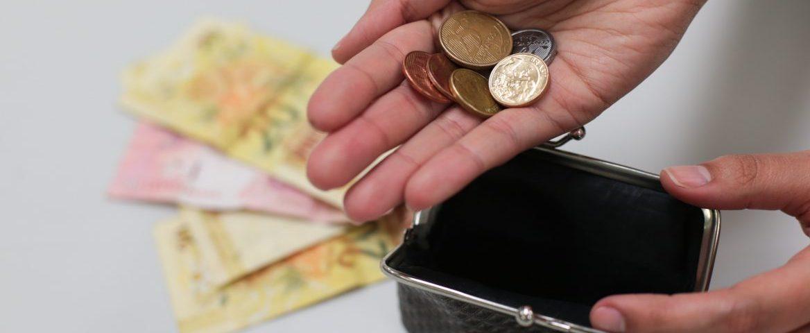 Duas mãos. Uma delas segura seis moedas de diversos valores. A outra abre uma pequena bolsa para guardá-las. Ao fundo, quatro notas de Real ─ três de vinte e uma de dez ─ estão sobre uma superfície branca.