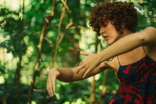 Uma mulher retratada da cabeça à cintura dança fazendo movimentos com os braços para a direita.