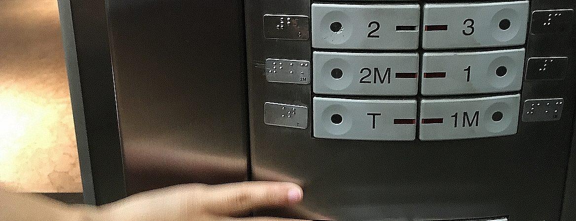 Mão segura elevador, com detalhe dos números dos andares aparecendo