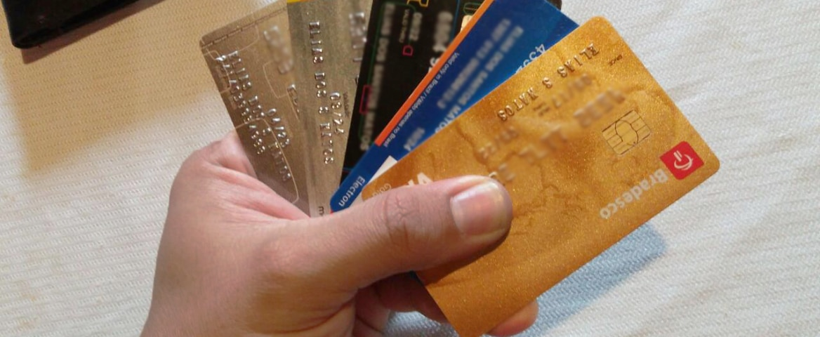 Uma mão segura cinco cartões de crédito.