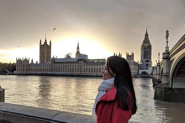 A universitária Letícia está em Londres, na frente do Rio Tâmisa e do Parlamento. Ela veste sobretudo vermelho e está com cachecol branco. Letícia tem cabelos pretos e está de perfil