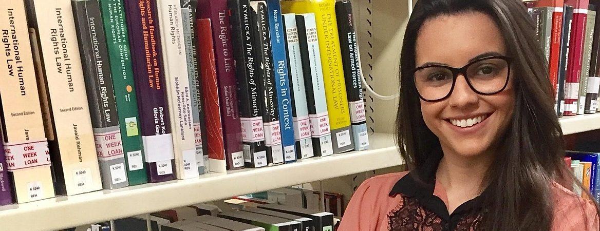 Letícia tem cabelos negros e usa óculos. Está com blusa rosada, dentro da biblioteca da faculdade em que fez mestrado, em Londres