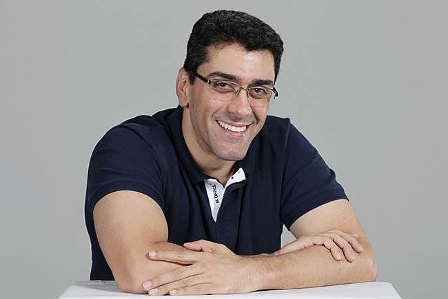 Luiz Alexandre Souza Ventura está com os braços cruzados apoiados em uma mesa. Ele veste camiseta polo azul marinho e usa óculos. Ele é moreno e tem olhos castanhos. O fundo da imagem é branco.