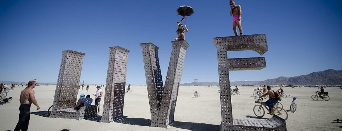 """Em um dia de céu claro no deserto, dois participantes do Burning Man posam para a foto em cima de uma instalação de arte feita em material metálico. A instalação forma a palavra """"live"""" e os dois homens estão um cima do v e outro em cima do e. Enquanto isso, outras pessoas caminham e andam de bicicleta ao fundo."""