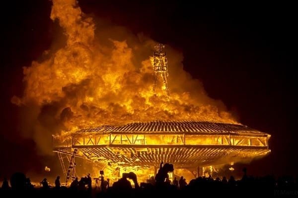 Uma enorme estrutura de madeira com formato de disco voador está completamente em chamas durante a noite. Em primeiro plano, embaixo, estão as silhuetas de algumas pessoas dançando.