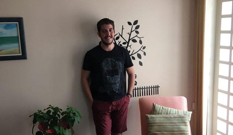 Gabriel Melani é moreno e possui barba curta. Ele está em pé, apoiado na parede, no meio de uma mesa com um vaso de flor e uma cadeira longa de descanso. Ele sorri. As mãos estão nos bolsos da bermuda, na cor vermelha. Ele usa camiseta preta e chinelos.