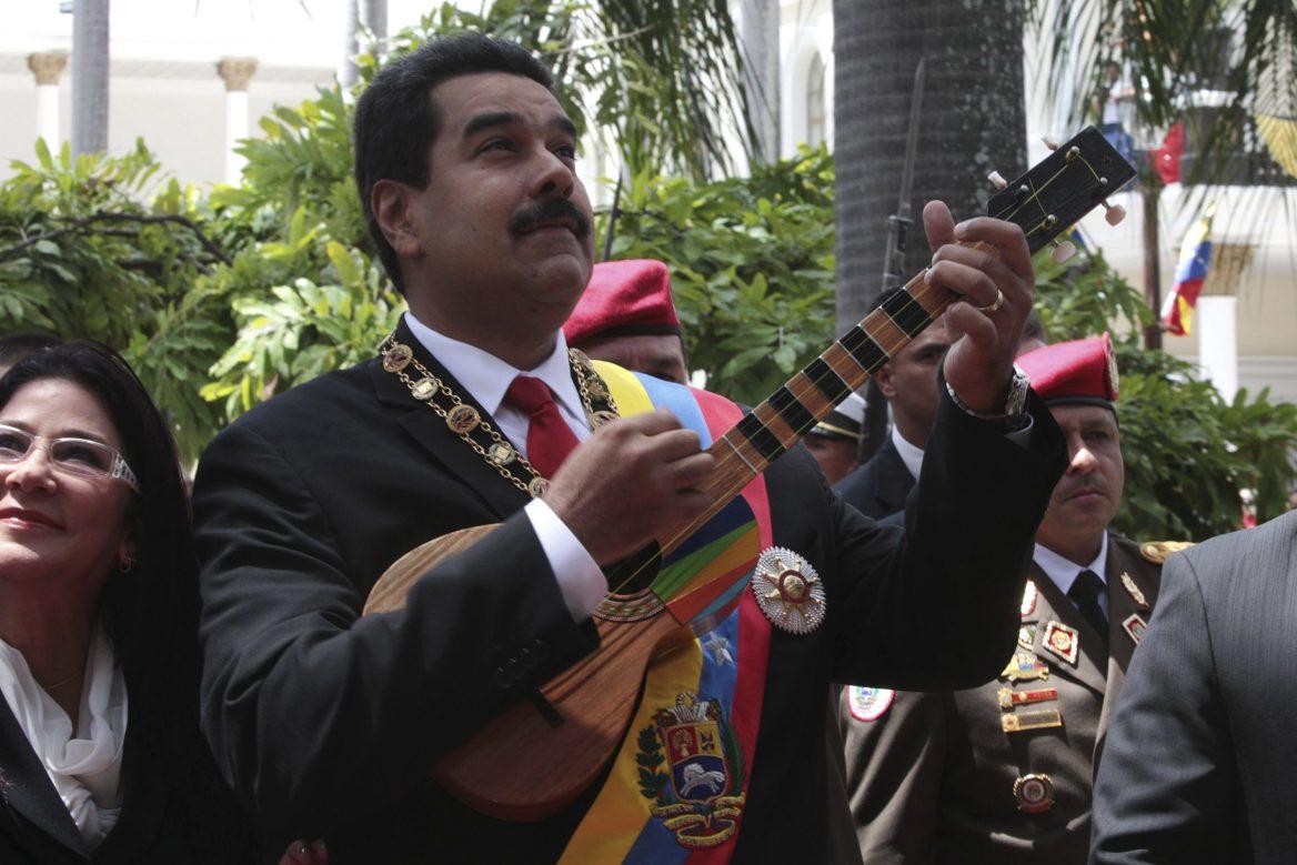 Nicolás Maduro veste um terno e a faixa presidencial da Venezuela, nas cores da bandeira, amarelo, azul e vermelho. Ele toca um instrumento musical típico do país, parecido com um violão, porém menor. Ao fundo, outras pessoas presenciam a cena.