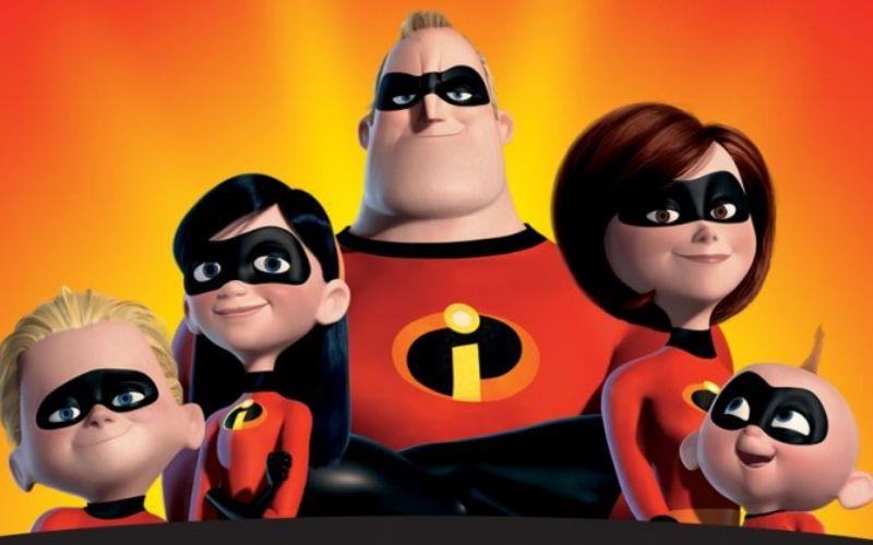 Da esquerda para a direita: Flecha, Violeta, Senhor Incrível, Mulher Elástica e Zezé, todos rindo e vestindo o uniforme oficial da família Incrível, em um fundo laranja.
