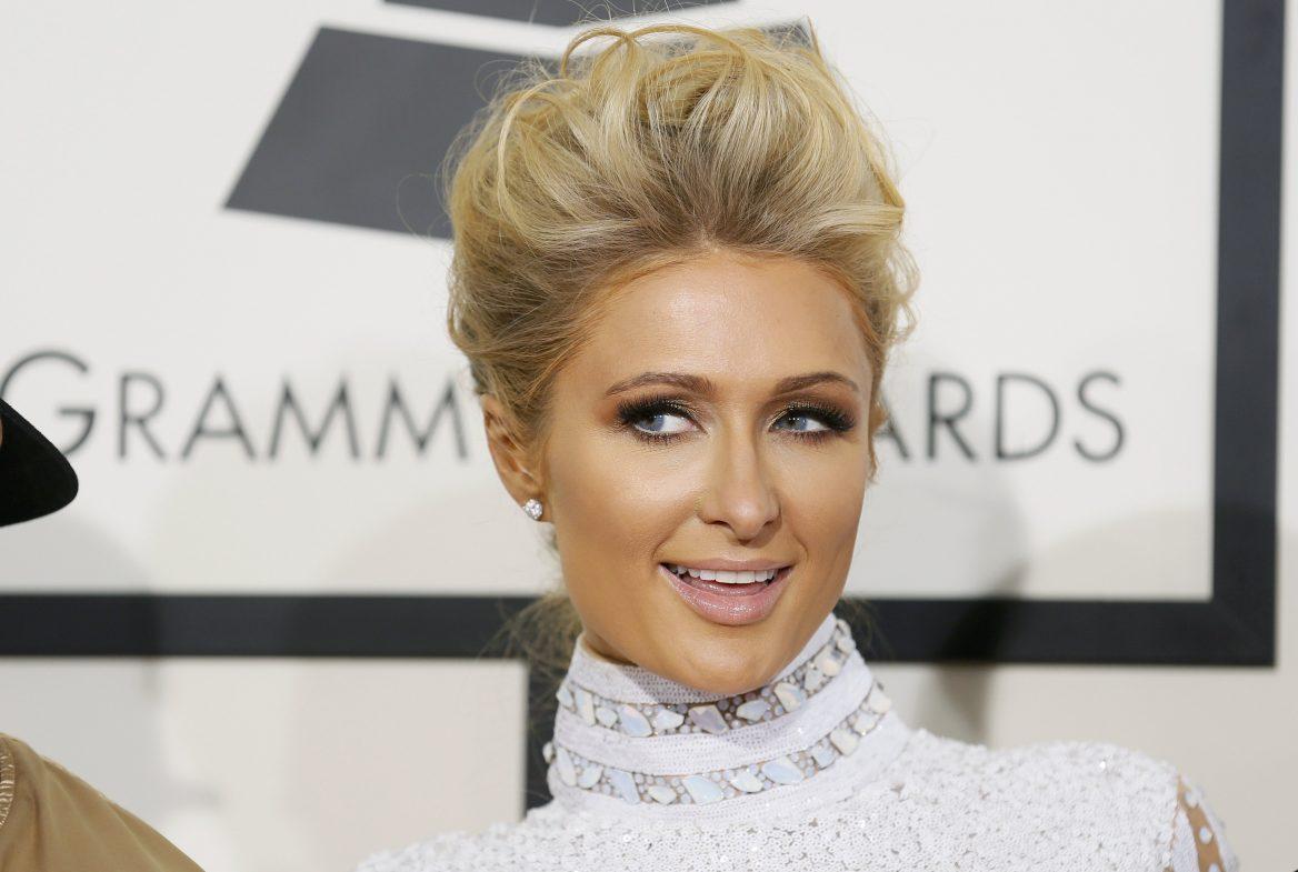 A socialite Paris Hilton sorri e olha para o lado esquerdo. Seu cabelo está preso em um penteado e ela usa um vestido de gola branca. Ao fundo, um painel com o símbolo e o nome do Grammy Awards.