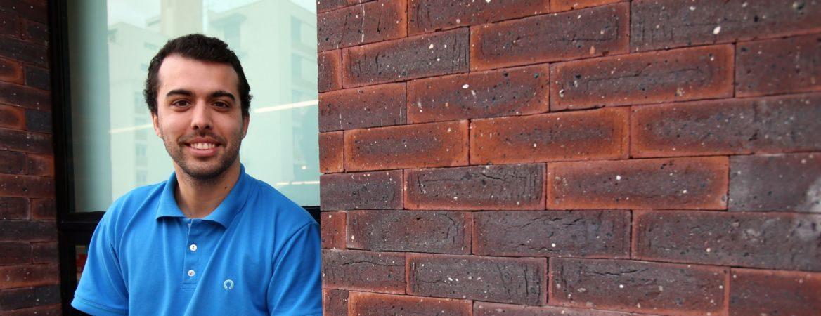 Pedro Conrade está sorrindo, sentado em frente a uma janela. Veste camiseta polo azul e tem cabelos castanhos escuros.