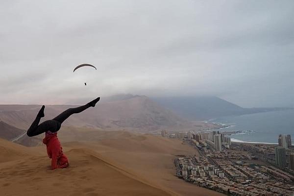 A viajante Eve Laako faz uma posição de ioga em cima de uma duna de areia no Chile. Do lado direito ao fundo está a cidade. Também do lado direito, mais ao fundo está o mar e algumas montanhas, parcialmente encobertas por neblina.