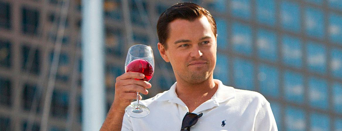 """O ator Leonardo DiCaprio como o personagem Jordan Belfort, protagonista do filme """"O Lobo de Wall Street"""". Ele está de pé e segura uma taça de vinho. Ele veste camiseta branca."""