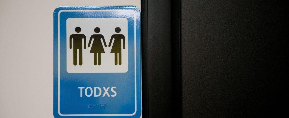 Placa mistura figuras masculina e feminina para mostrar que qualquer pessoa pode usar o banheiro.