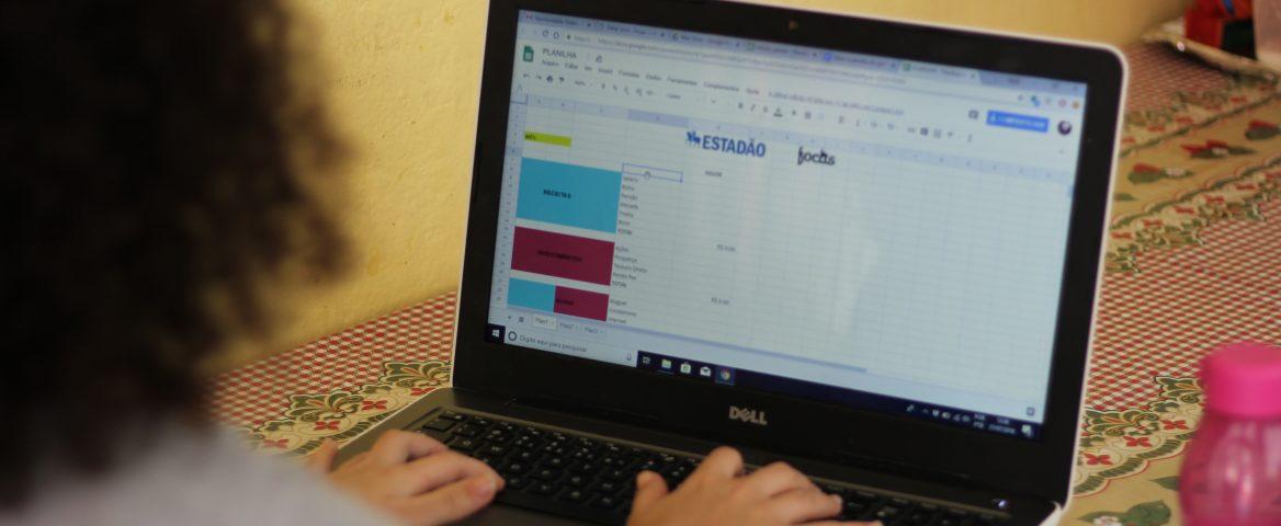 Menina mexe em um notebook sobre uma mesa. Nele, há uma planilha de Excel aberta. Ao lado do notebook, há um celular branco e uma garrafinha rosa.