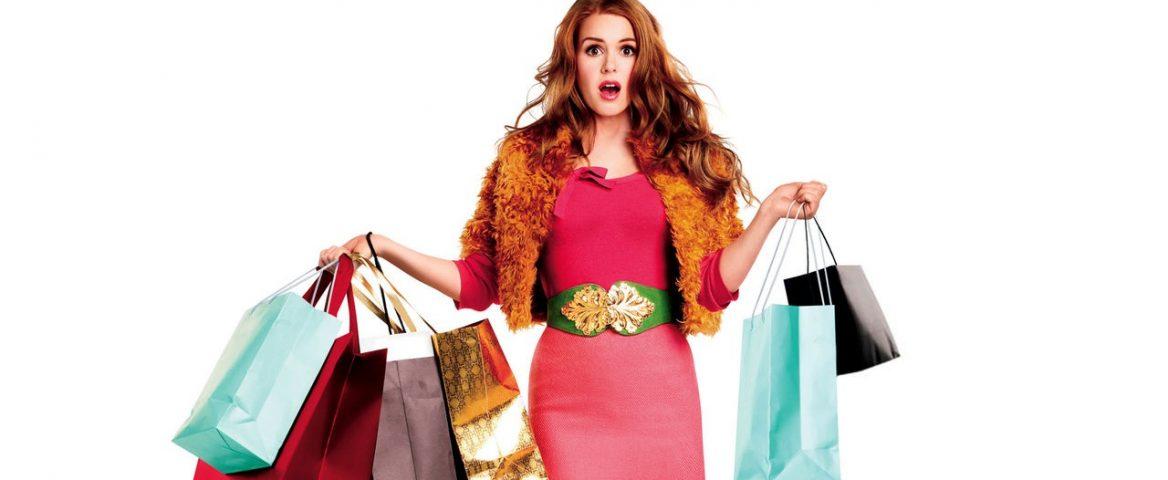 Mulher usa vestido rosa e segura várias sacolas de compras nas mãos. Ela é ruiva e tem cabelos longos. O fundo da imagem é branco.