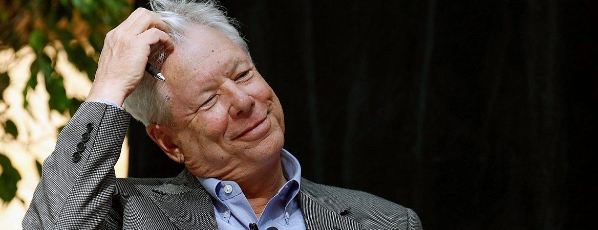 Richard Thaler, prêmio Nobel de Economia em 2017, é grisalho e veste terno cinza com camisa branca. Ele está sorrindo e mexendo no cabelo com a mão direita