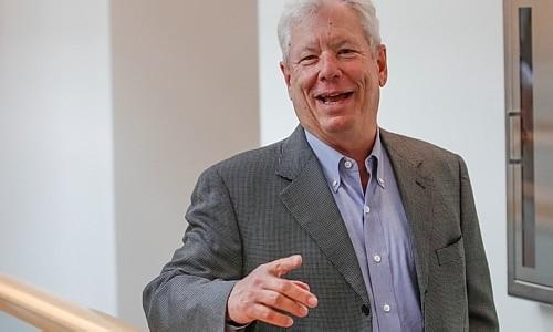 Richard Thaler é grisalho e está sorrindo para a foto. Ele veste terno cinza e camisa social azul